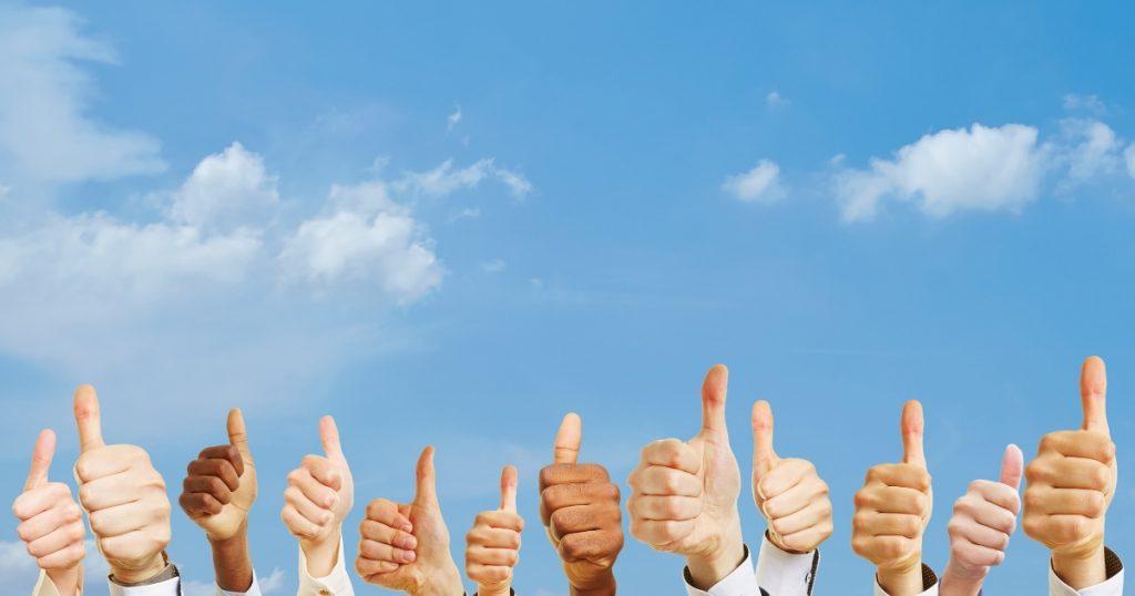 空に向かって親指を掲げる人の手