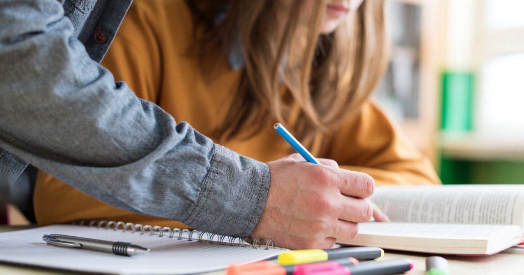 男性が鉛筆でテキストに書き込んでいる様子
