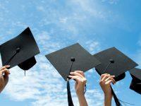 卒業帽子を空に掲げている様子
